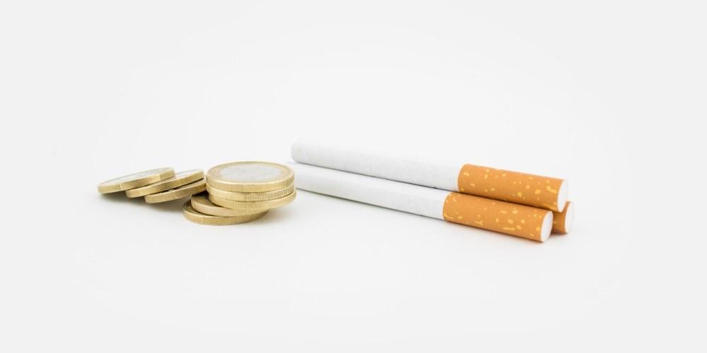 Zigarette neben Münzen - Mit dem Rauchfrei-Rechner kann man die Ausgaben ausrechnen