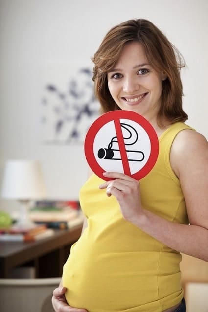 Frau zeigt ein Rauchverbotsschild und sagt aus, dass das Passivrauchen Schwangerschaft und Kind schadet