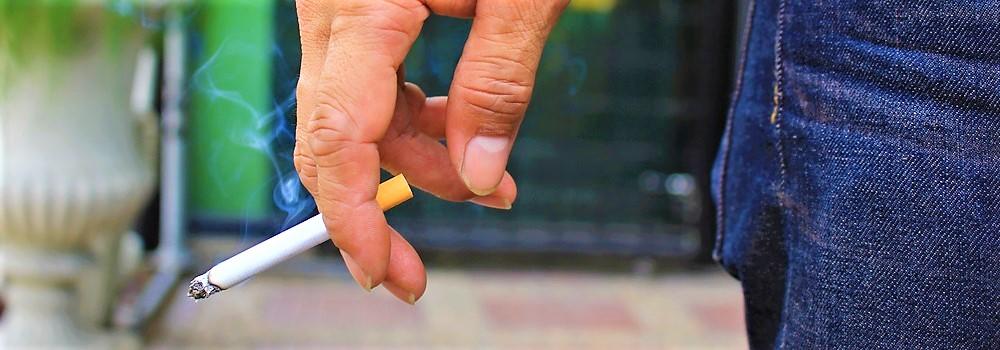 Mann hat gelbe Fingernägel und raucht