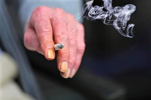 Mann qualmt eine Zigarette und hat gelbe Finger vom Rauchen