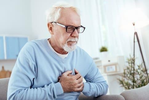 Mann fasst sich an die Brust (Herz)