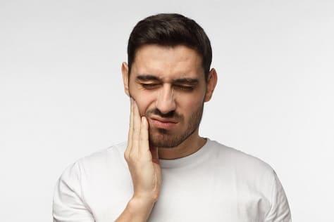 Mann spürt die Nebenwirkungen vom Nikotinkaugummi und fasst sich an den Kiefer