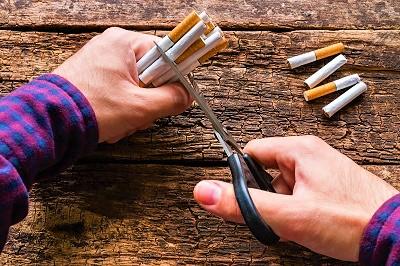 Mann zerschneidet Zigaretten