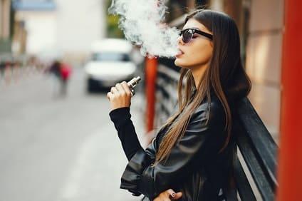 Frau dampft auf der Straße, obwohl sie eigentlich mit dem Dampfen aufhören will