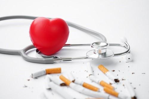 Plastik-Herz liegt neben Zigaretten