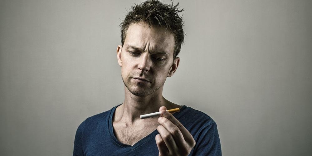 Mann schaut Zigarette an und fragt sich, warum man eigentlich raucht