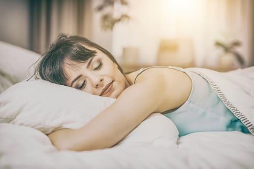 Frau schläft tief und fest, um Müdigkeit im Alltag zu vermeiden