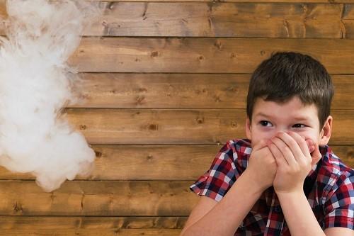 Junge bekommt Passivrauch ab und hält sich die Nase und den Mund zu