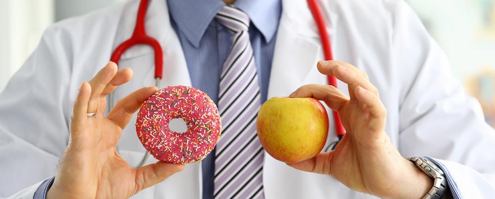 1 arzt im weißem Kittel hält apfel und doughnut in der hand als konzept für eine ausgewogene ernährungs mit kalorienrechner
