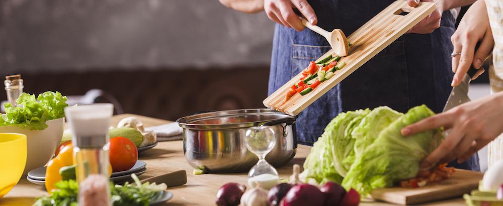 2 mann und frau kochen zusammen und geben tipps zur gesunden ernährung