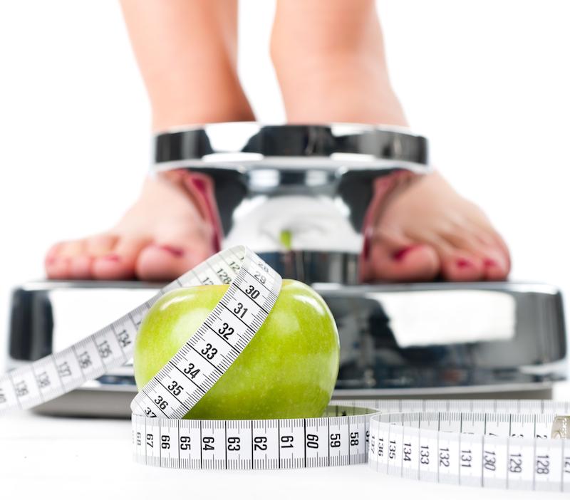 BMI Rechner frau steht auf wage mit apfel und maßband