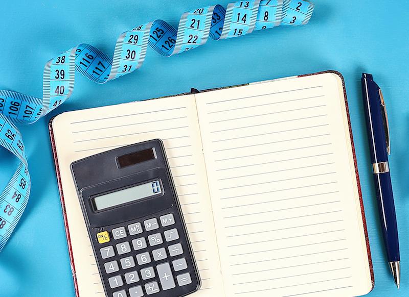 1 gesunder lifestyle konzept mit Taschenrechner notitzbuch und maßband als kalorienrechner