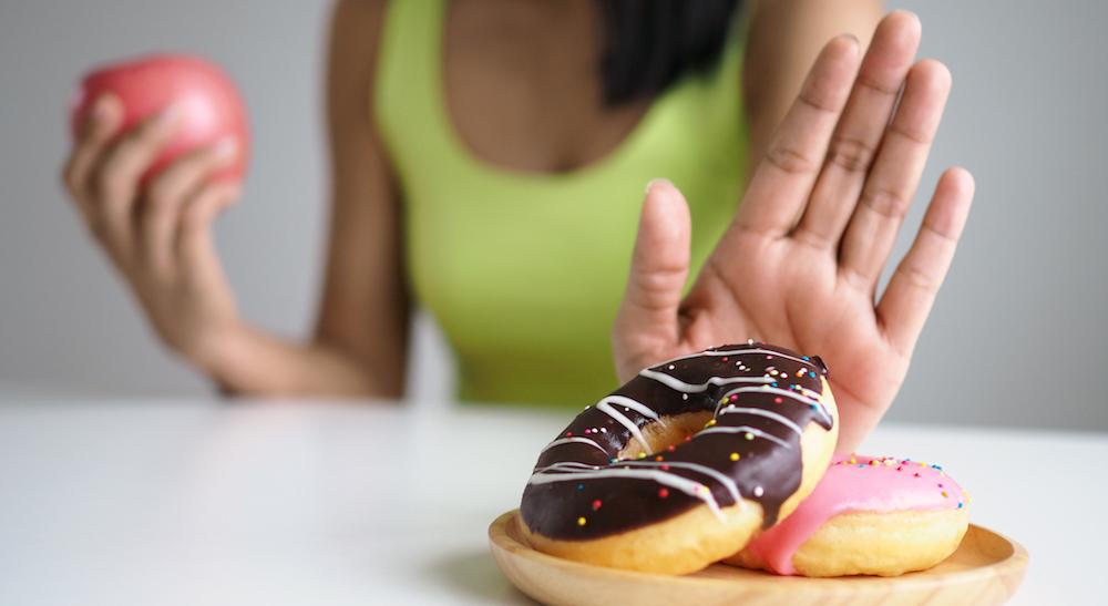 frau isst einen apfel als gesunde zwischenmahlzeit und drückt süße doughnuts weg
