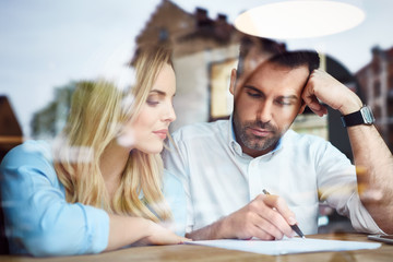 Couple at cafe reading bank contract document