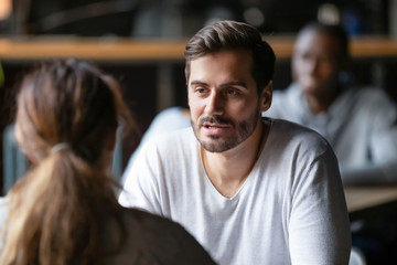 Young serious man having conversation with woman girlfriend in cafe
