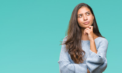 Young beautiful arab woman wearing winter sweater over isolated background with hand on chin thinking about question, pensive expression. Smiling with ...