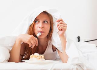 Meadchen isst Kekks in Ihrem Bett