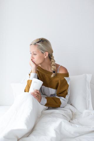 """Junge Frau denkt an """"warum werde ich nicht schwanger"""" und trinkt Tee im Bett"""
