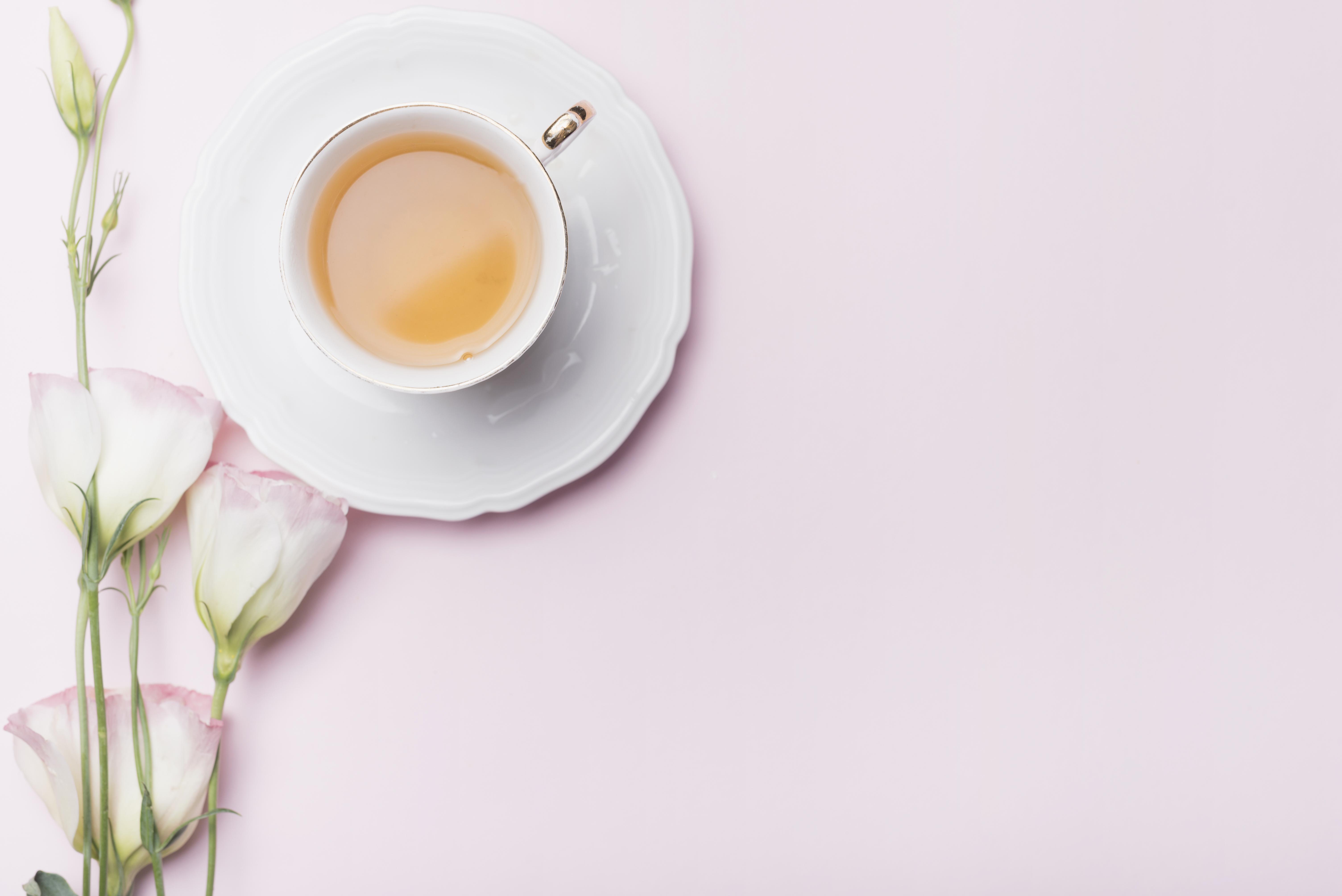 Weiße Teetasse neben weißer Blume