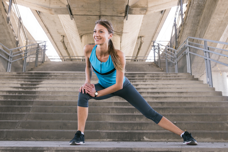 Frau in Fitnessklamotten macht Dehnübung vor Steintreppe