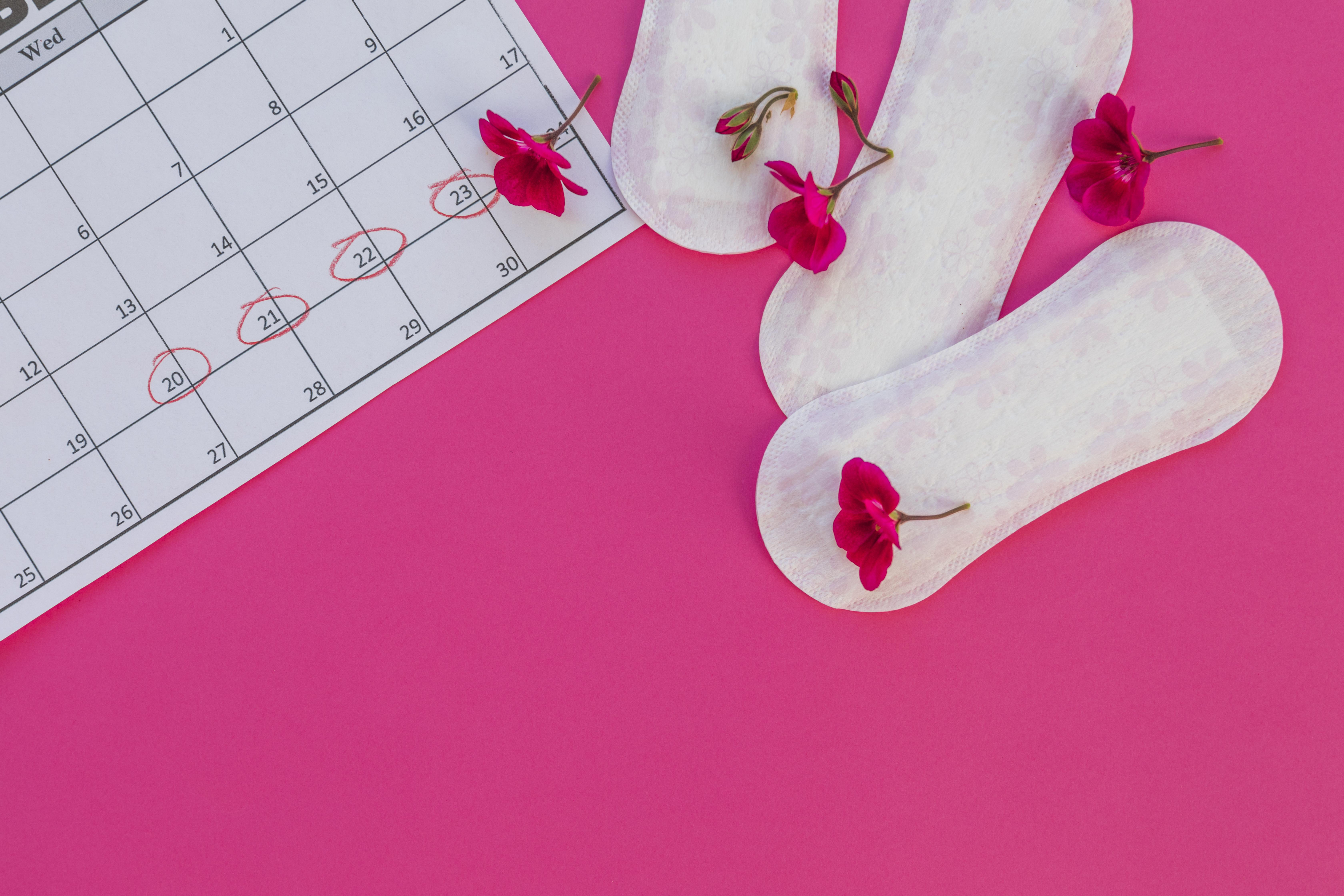 Kalender mit markierten Tagen, Damenbinde und Blumen