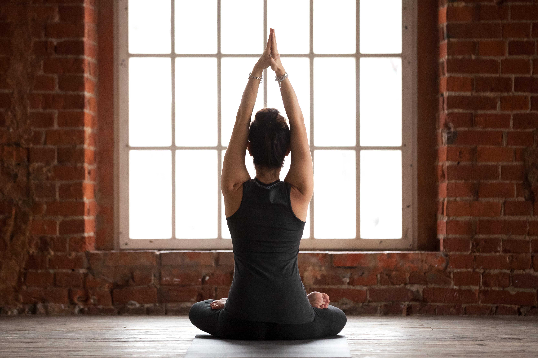 Frau meditiert im Sitzen mit und streckt ihre Arme zur Decke
