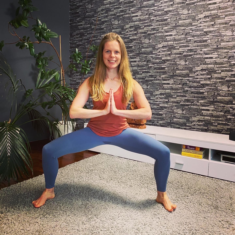 Frau im Sportoutfit steht in Yoga-Pose auf einem Teppich. Im Hintergrund sind große Pflanzen und eine Buddha-Figur zu sehen.