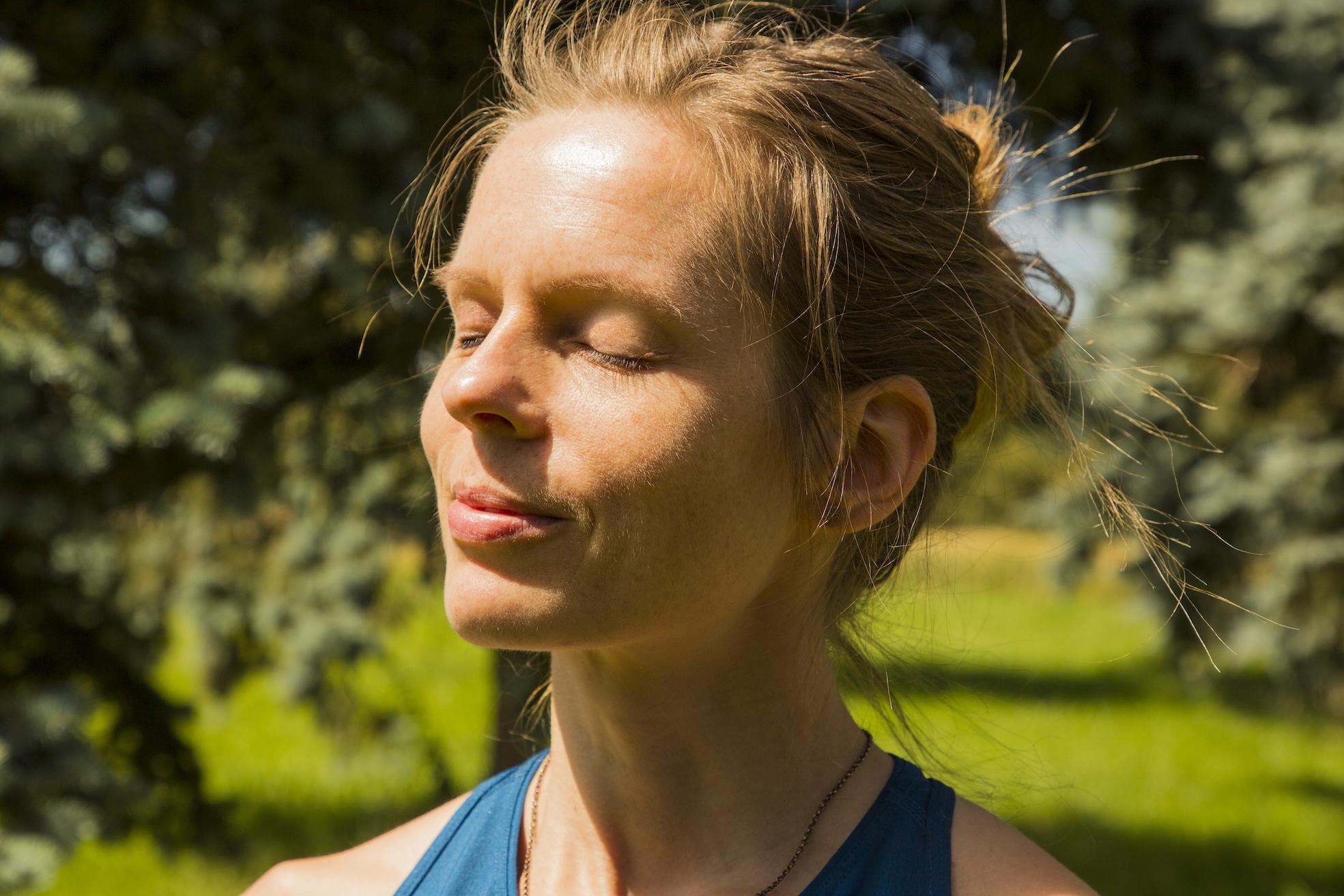 Frau mit hoch gebundenen Haaren steht in der Natur und genießt mit geschlossenen Augen die Sonne im Gesicht.
