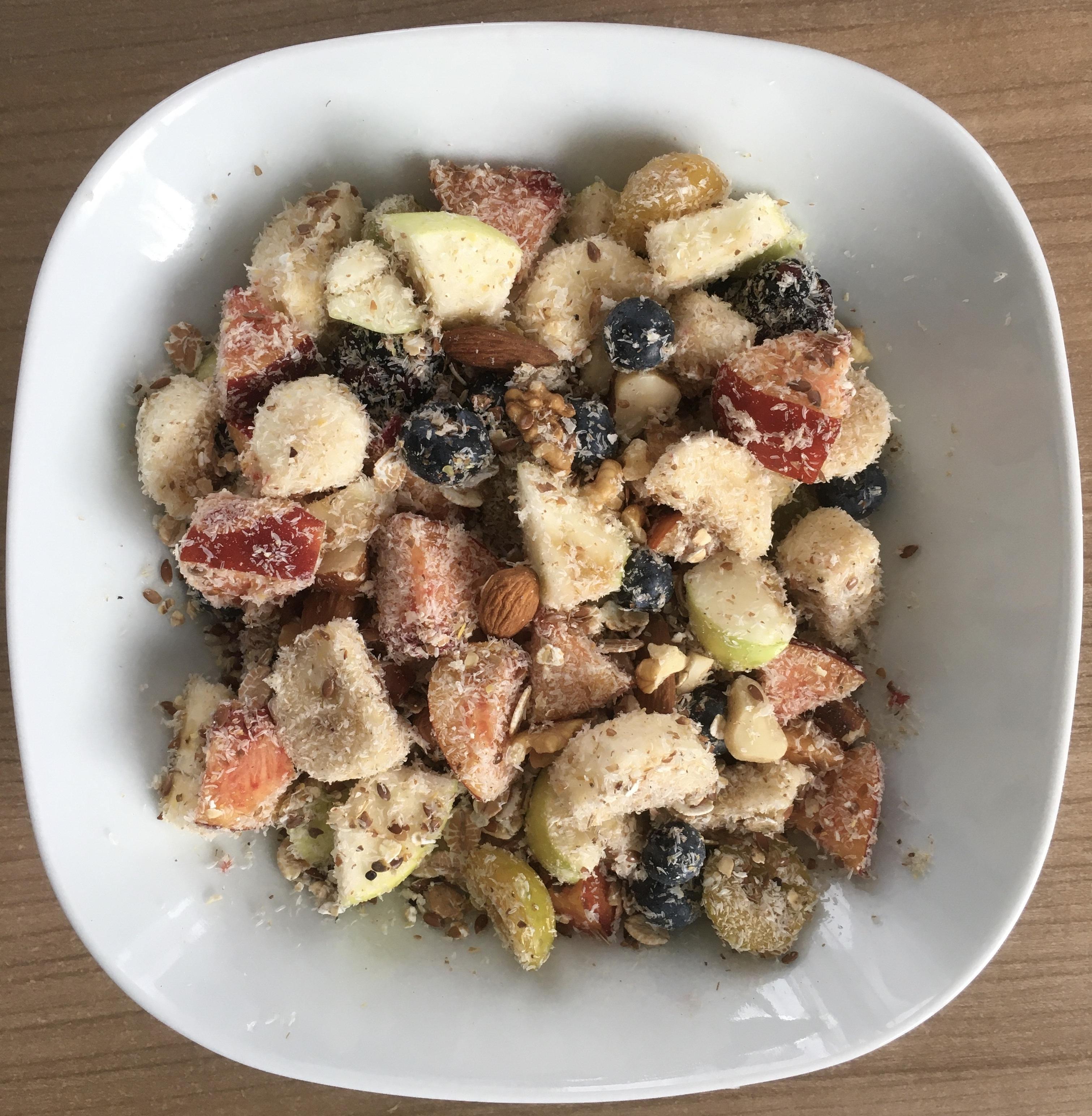 Ein Teller mit Müsli aus Obststücken, Kernen, Nüssen und mit Hafermilch.
