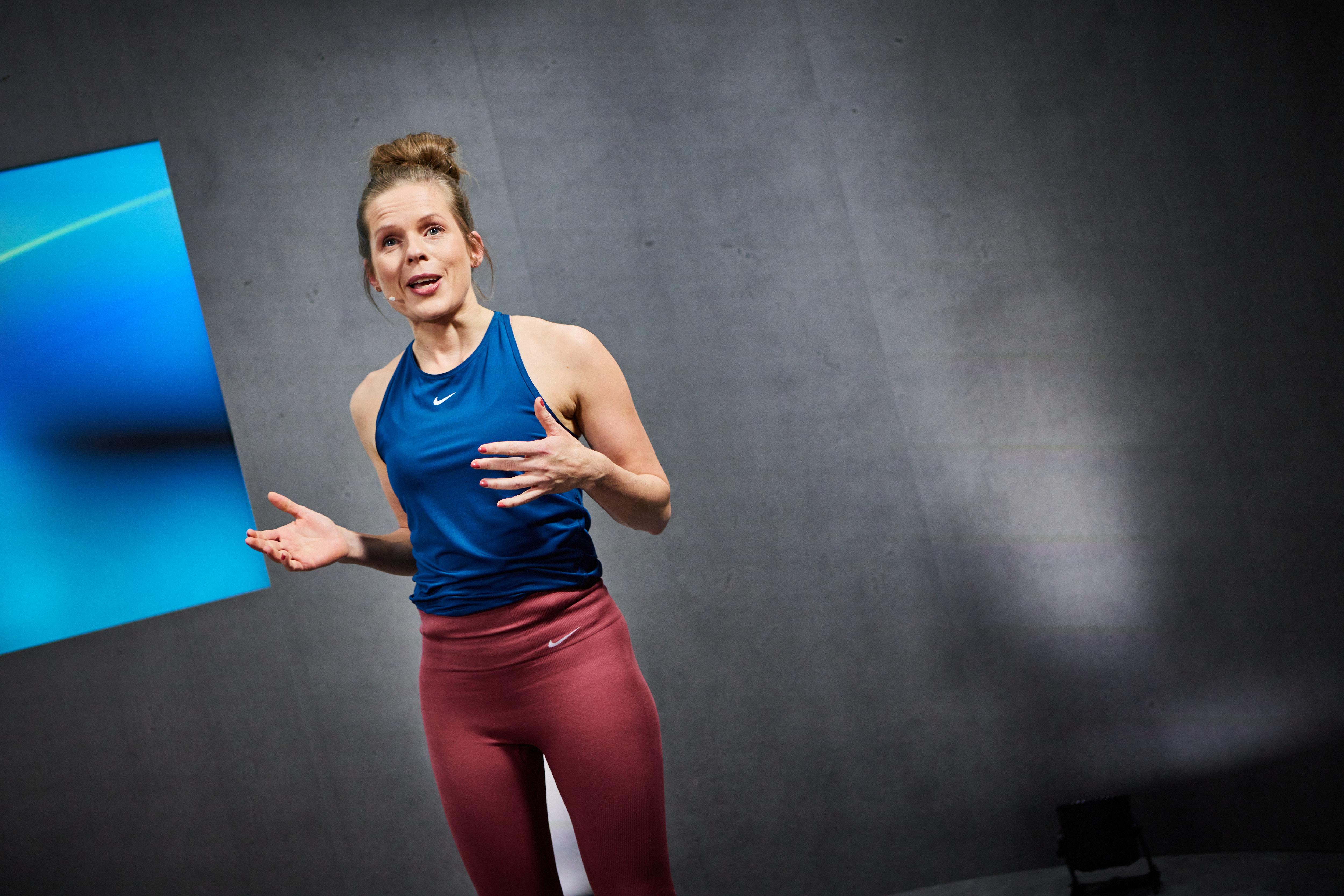 Eine Frau im Sportoutfit steht vor einer Kamera und hält eine Rede. Die Umrisse der Kamera sind nur verschwommen im Vordergrund erkennbar.