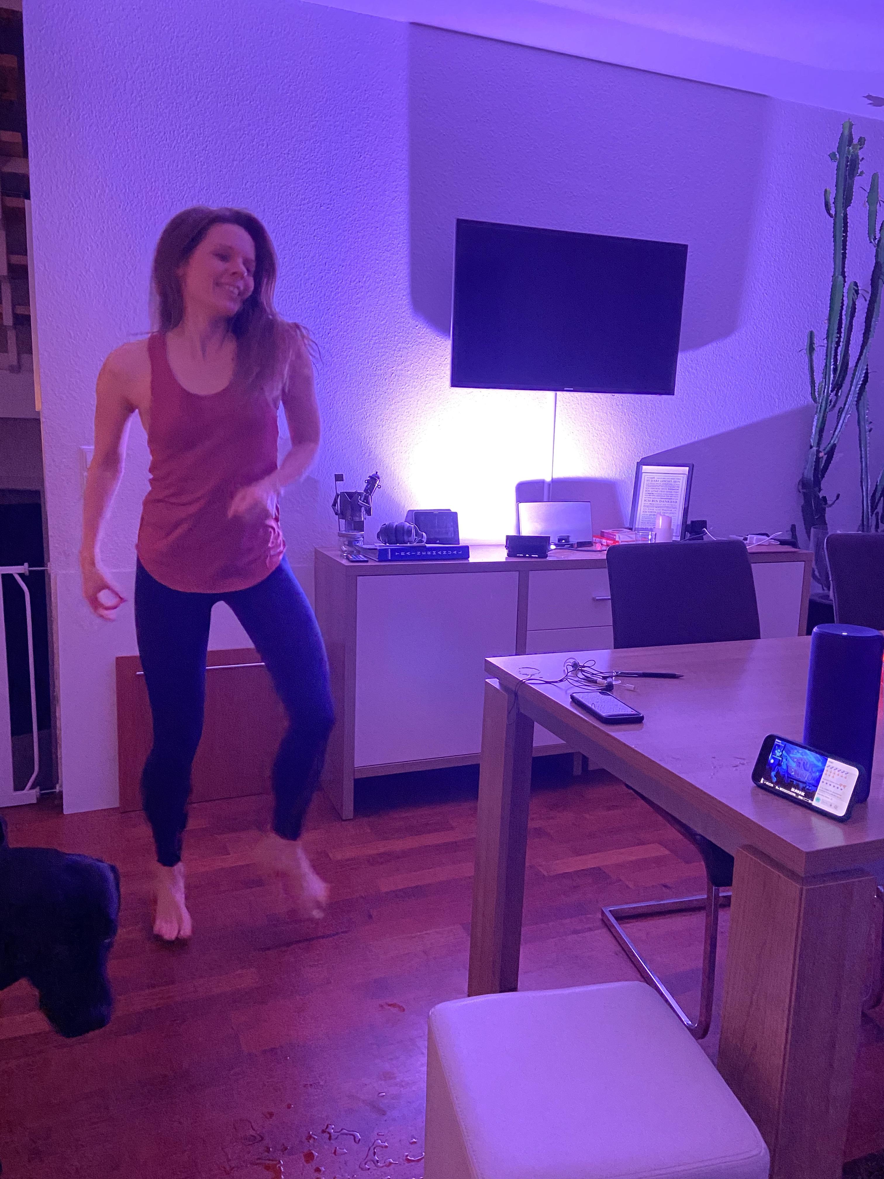 Frau im Sportoutfit tanzt ausgelassen in einem Esszimmer. Das Zimmer wird von Discobeleuchtung erhellt.