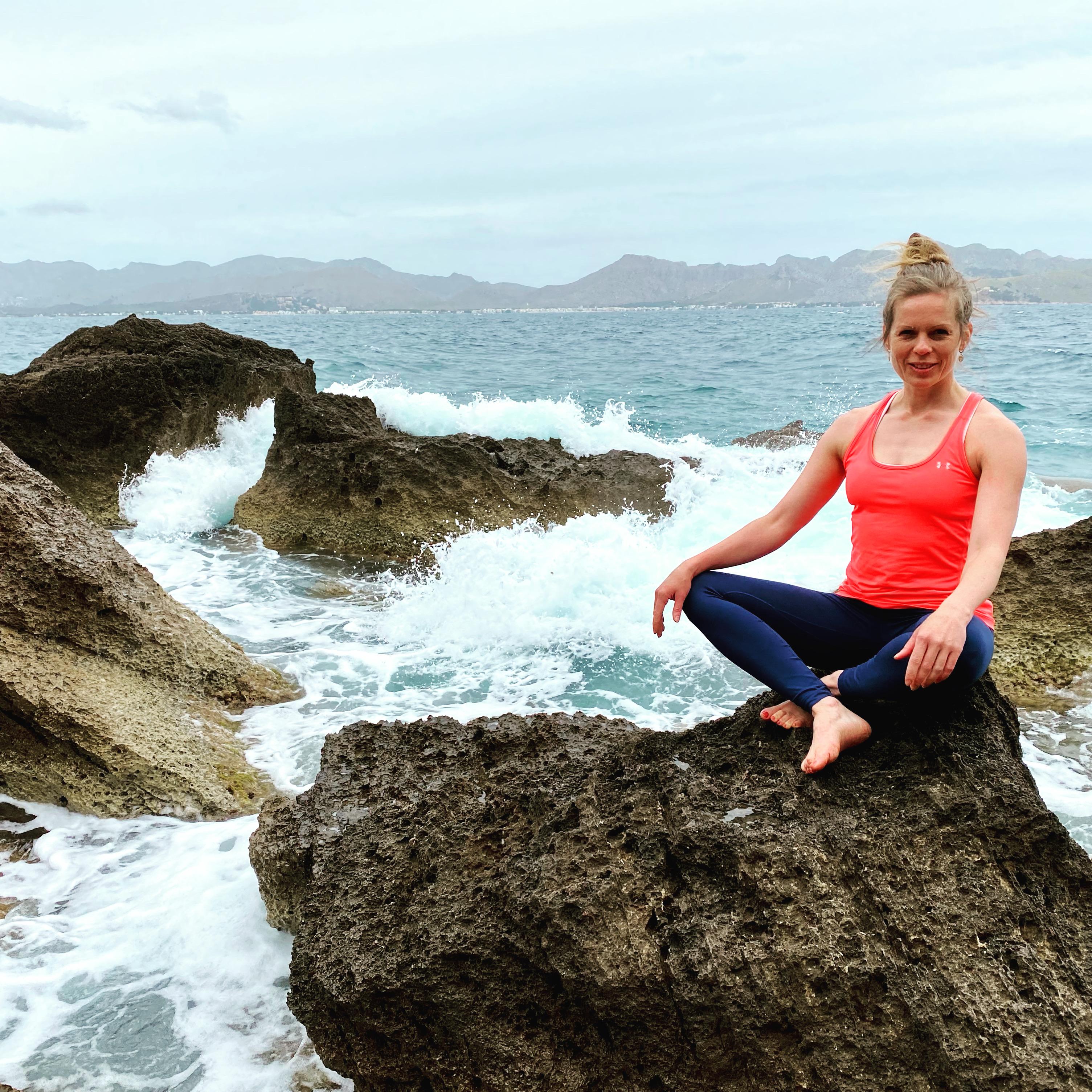 Frau im Sportoutfit sitzt im Schneidersitz auf einem Stein. Um sie herum sind weitere große und kleine Felsen. Im Hintergrund ist ein tosendes Meer zu sehen. Es ist sehr windig.