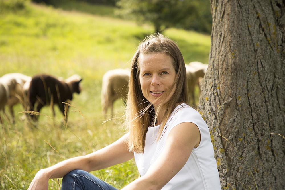 Frau sitzt an einem Baum und lächelt in die Kamera. Im Hintergrund läuft eine Herde Schafe vorbei.