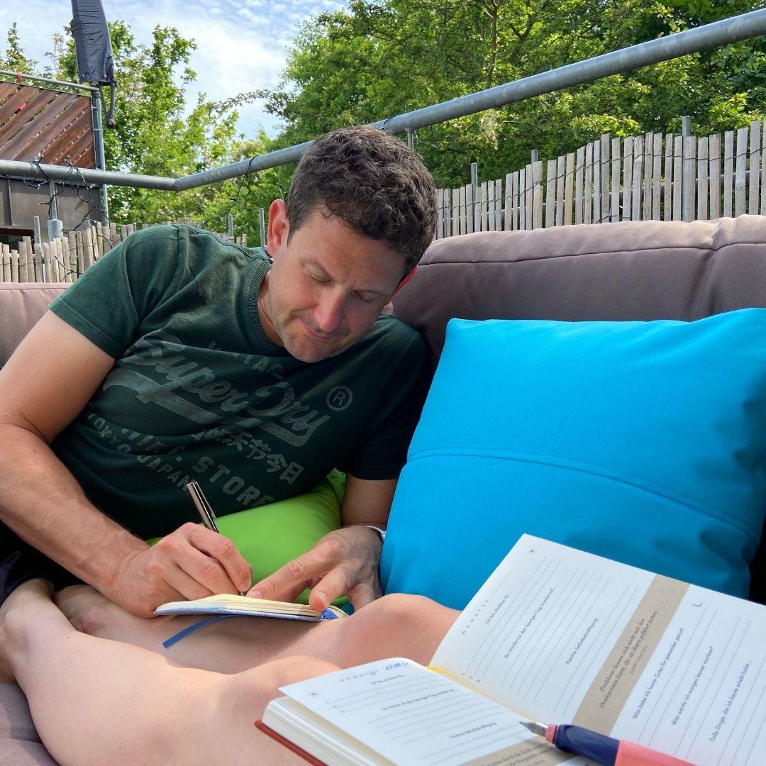 Mann sitz auf Sitzecke auf einer Terrasse und schreibt in sein Tagebuch.