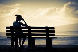Frau auf einer Bank mit Liebeskummer