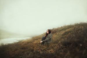 Frau sitzt mit Einsamkeit allein auf einer Wiese
