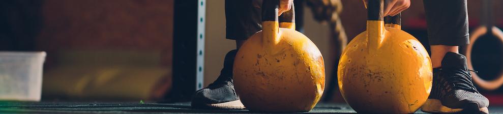 beschnittener-schuss-des-maennlichen-athleten-der-uebungen-mit-kesselglocke-macht-gewichtheben-krafttraining-und-cross-fit-ausruestung-sport-fitnesskonzept