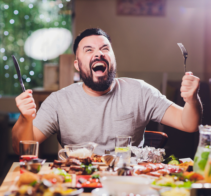 glücklicher mann-am-grossen-tisch-mit-essen