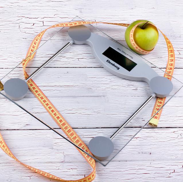 gruener-apfel-orangefarbenes-massband-auf-glaswaagen-liegen