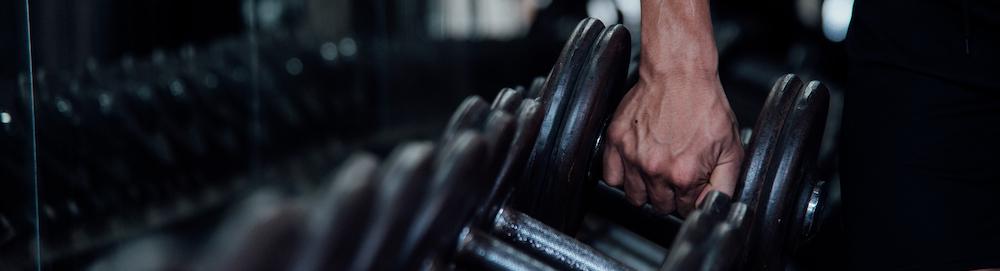 Kurzhantel Seitenansicht im Gym wird von Mann angehoben