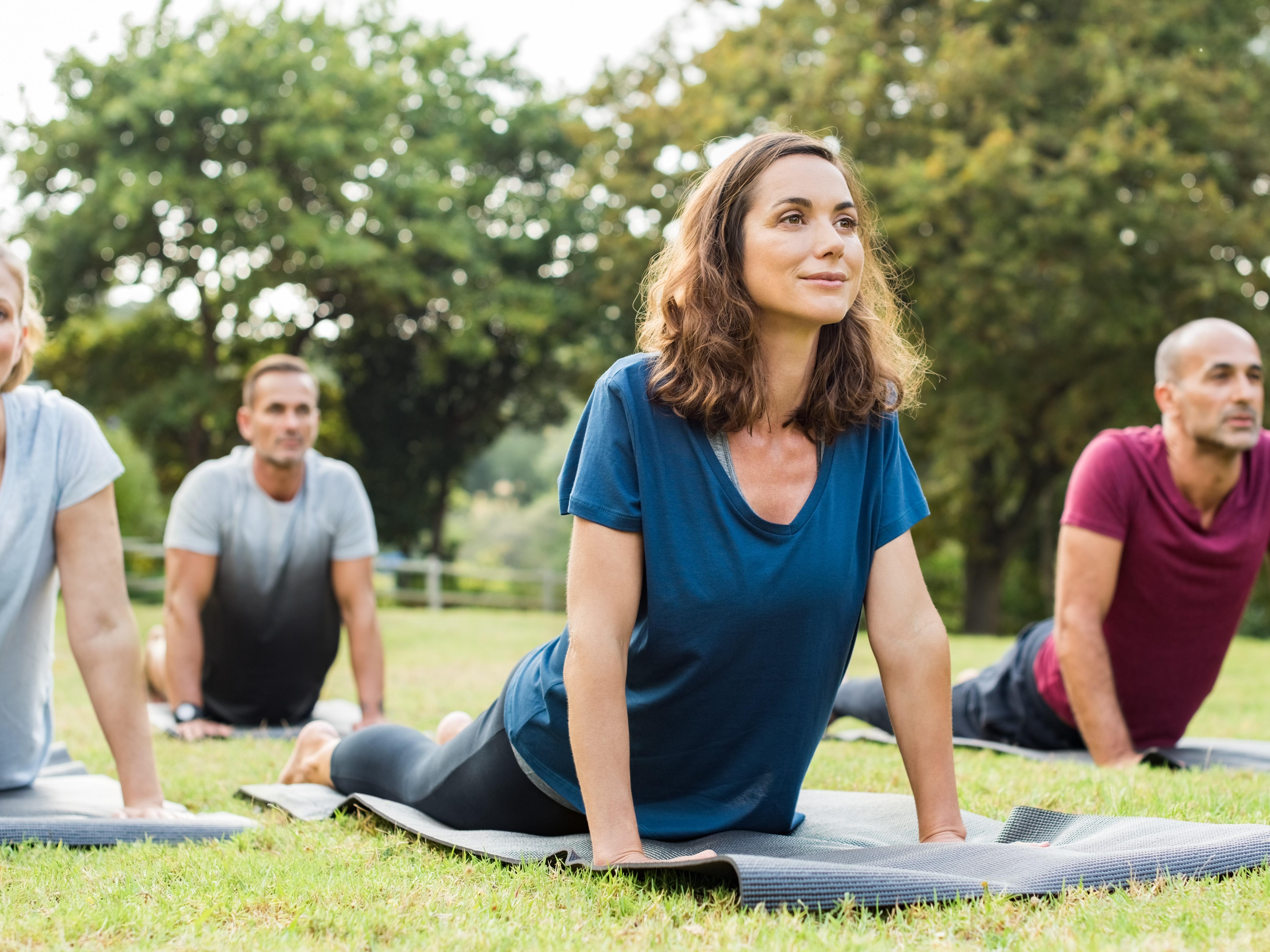 Rückenübungen, Menschen auf Gymnastikmatten in einem Park