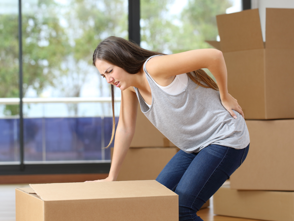 Eine Frau die versucht schwere Kartons zu heben