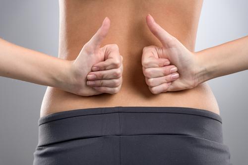 Keine Rückenschmerzen. Rückseite der Frau mit Daumen nach oben