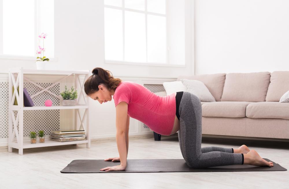 Junge schwangere Frau, die zu Hause Yoga praktiziert