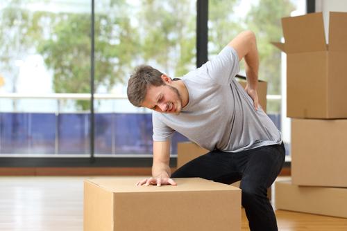 Mann mit Rückenschmerzen, hebt Kisten in seinem neuen Haus