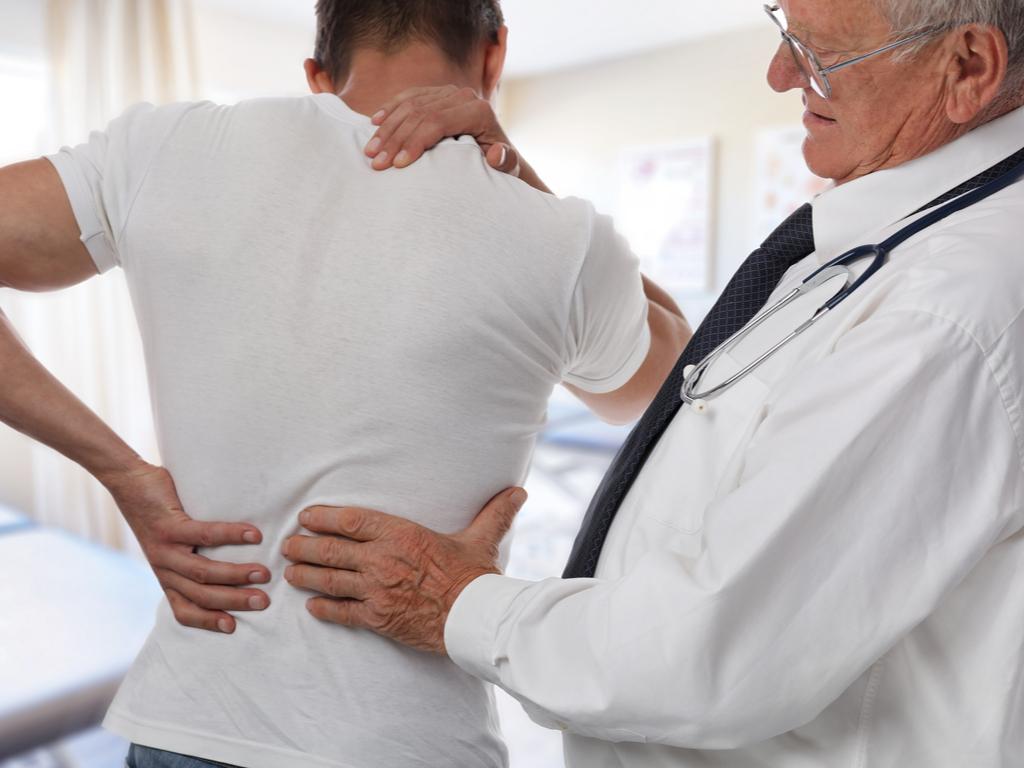 Männlicher Arzt und Patient, während einer ärztlichen Untersuchung am Rücken