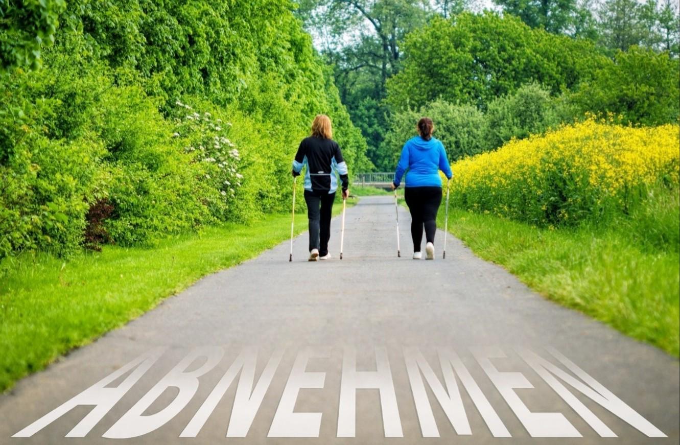 Zwei Frauen, die Nordic Walking machen