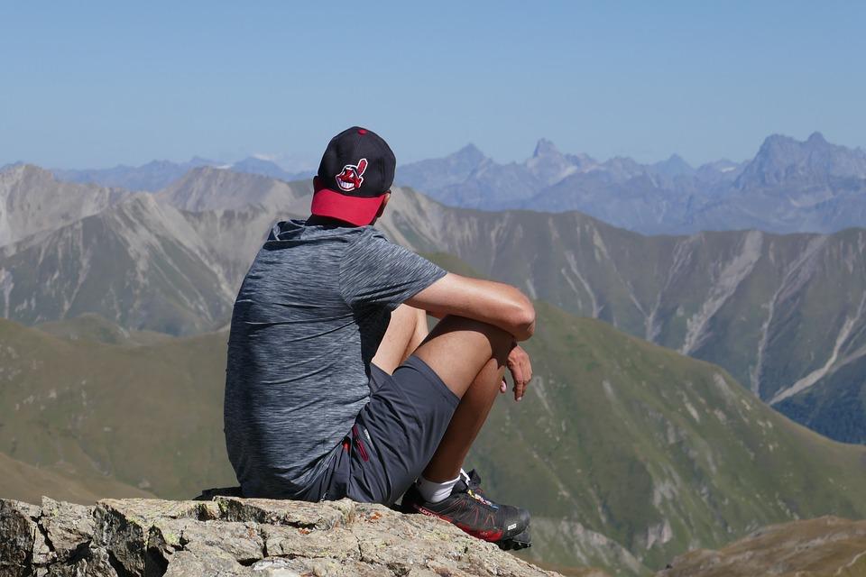 Dieser Mann sitzt in den Bergen um sein Stresslevel aktiv zu reduzieren