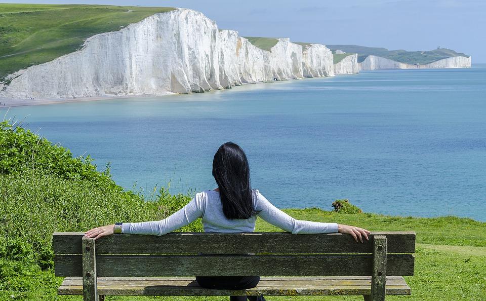 Diese Frau sitzt auf einer Bank mit Blick auf das schöne Meer und baut dabei ihren Stress ab