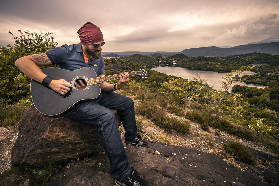 Dieser Mann spielt Gitarre in der Natur und senkt dabei seinen Stresspegel